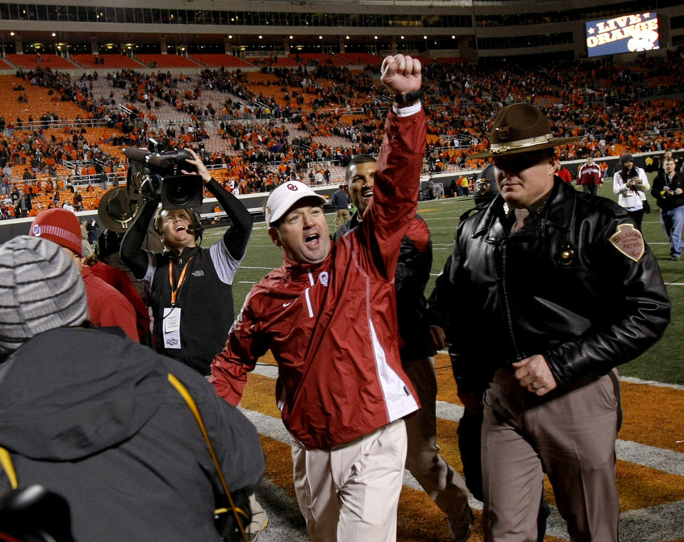 Photo - OU coach Bob Stoops celebrates after the Bedlam college football game between the University of Oklahoma Sooners (OU) and the Oklahoma State University Cowboys (OSU) at Boone Pickens Stadium in Stillwater, Okla., Saturday, Nov. 27, 2010. Photo by Bryan Terry, The Oklahoman