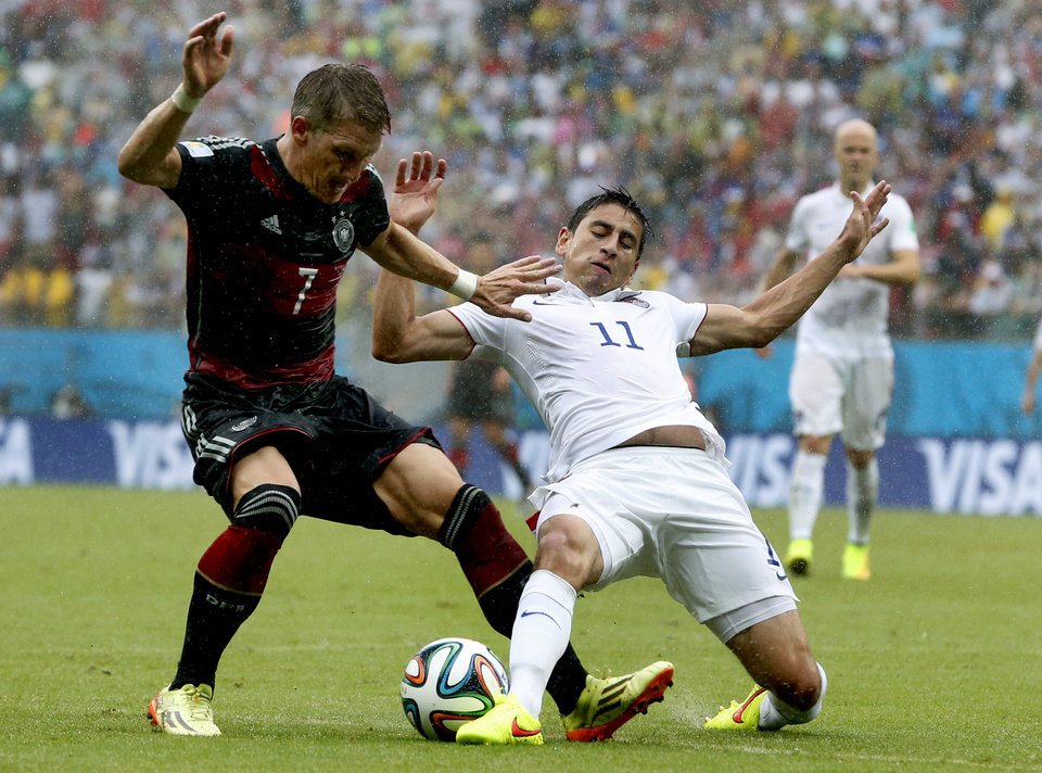 Photo - Germany's Bastian Schweinsteiger, left, is challenged by United States' Alejandro Bedoya, right, during the group G World Cup soccer match between the USA and Germany at the Arena Pernambuco in Recife, Brazil, Thursday, June 26, 2014. (AP Photo/Matthias Schrader)