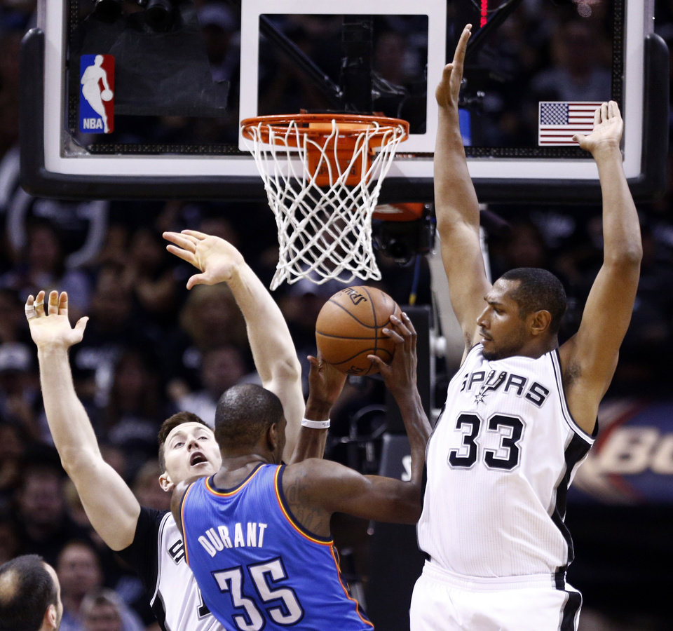 Photo - Oklahoma City's Kevin Durant (35) is called for a charge as San Antonio's Aron Baynes (16) and San Antonio's Boris Diaw (33) defends during Game 1 of the Western Conference Finals in the NBA playoffs between the Oklahoma City Thunder and the San Antonio Spurs at the AT&T Center in San Antonio, Monday, May 19, 2014. Photo by Sarah Phipps, The Oklahoman