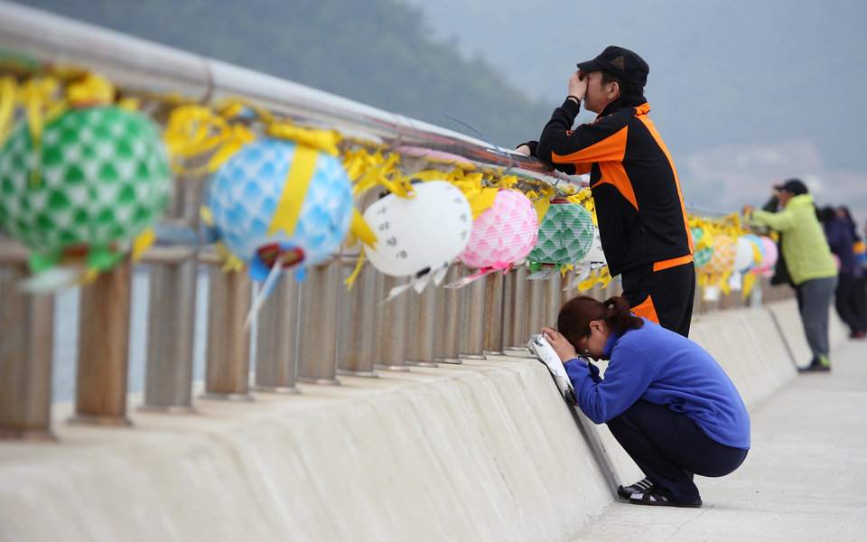 Photo - Relatives of a passenger aboard the sunken ferry Sewol weep at a port in Jindo, South Korea, Thursday, May 8, 2014. South Korean prosecutors said they have detained the head of the company that owns the ferry that sank last month over an allegation of cargo overloading.(AP Photo/Yonhap)   KOREA OUT