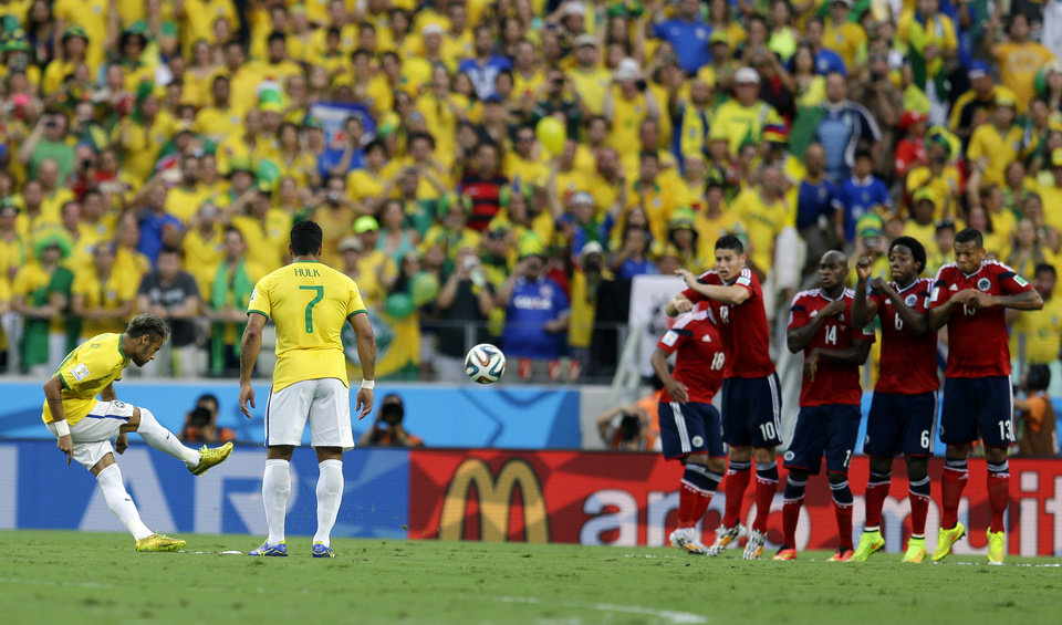 Photo - Brazil's Neymar takes a free kick against Colombia's defensive wall during the World Cup quarterfinal soccer match between Brazil and Colombia at the Arena Castelao in Fortaleza, Brazil, Friday, July 4, 2014. (AP Photo/Natacha Pisarenko)