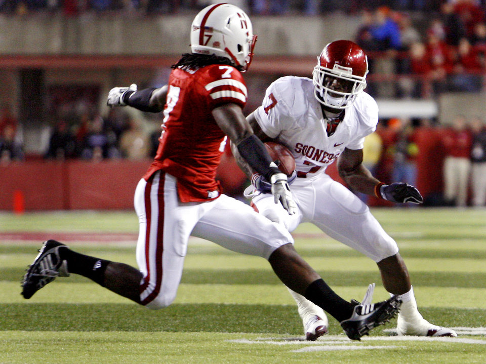 Photo - Oklahoma's DeMarco Murray (7) tries to get past Nebraska's Dejon Gomes (7) during the first half of the college football game between the University of Oklahoma Sooners (OU) and the University of Nebraska Cornhuskers (NU) on Saturday, Nov. 7, 2009, in Lincoln, Neb.  Photo by Chris Landsberger, The Oklahoman ORG XMIT: KOD