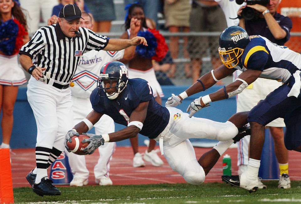Photo - Kansas running back John Randle (1) dives for a touchdown past Toledo free safety Patrick Body (11) during the first quarter in Lawrence, Kan., Saturday, Sept. 11, 2004. Side judge Jeff Ulery, left, is in position for the call. Randle took an Adam Barmann pass 55 yards for the score. (AP Photo/Orlin Wagner)  ORLIN WAGNER - ASSOCIATED PRESS