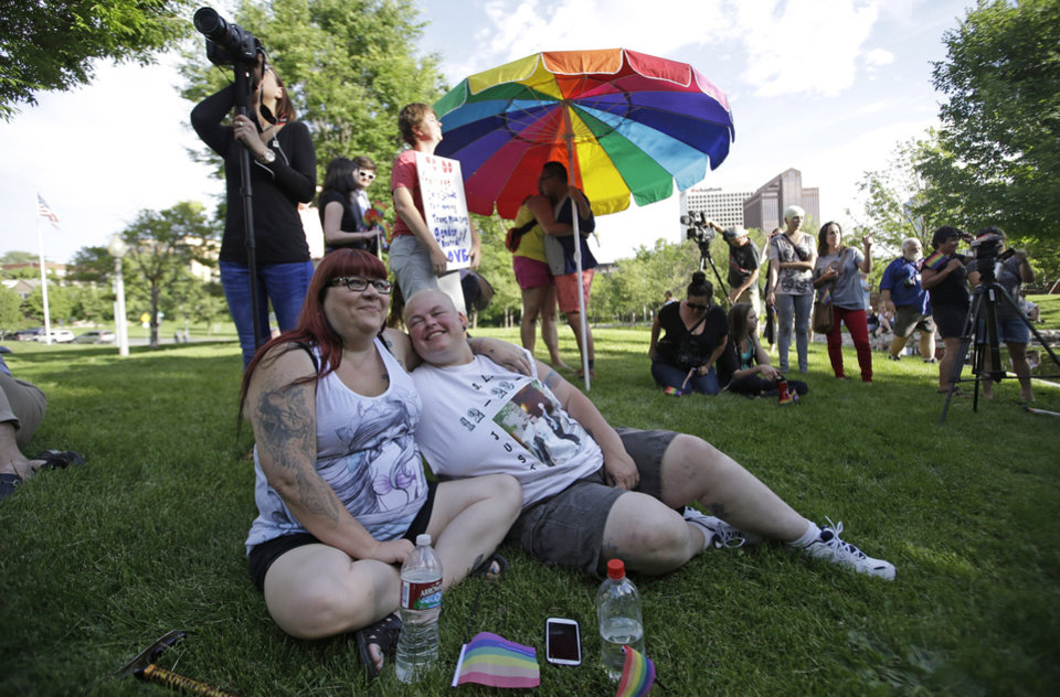 Photo - Dee Williams, right, and her spouse Angie Braithwaite looks on as wait  gather with people in a downtown park to celebrate the gay marriage ruling Wednesday, June 25, 2014, in Salt Lake City. Williams and Braithwaite were married Dec. 23rd, 2013. A federal appeals court on Wednesday ruled for the first time that states must allow gay couples to marry, finding the Constitution protects same-sex relationships and putting a remarkable legal winning streak across the country one step closer to the U.S. Supreme Court. (AP Photo/Rick Bowmer)