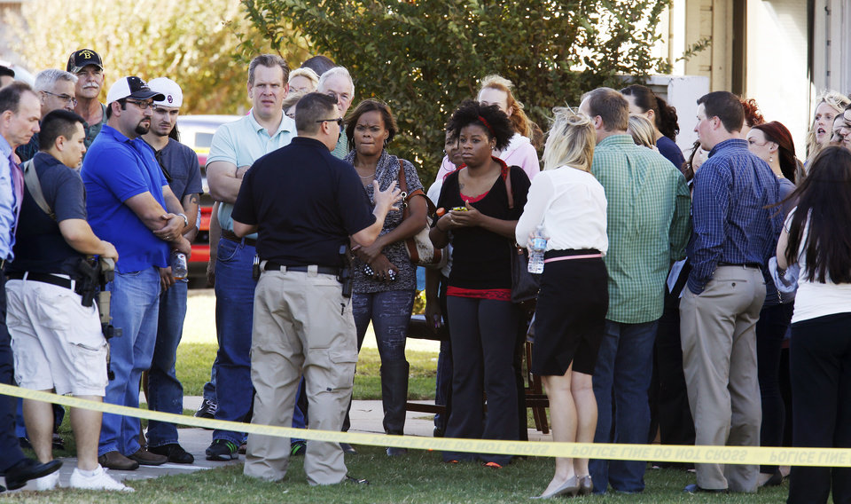 Photo - A police officer talks to workers from a nearby office building as they wait in a holding area at the Apple Creek Apartments near the scene of a hostage situation at Nextep in Norman Monday, Nov. 10, 2014.  Photo by Paul B. Southerland, The Oklahoman