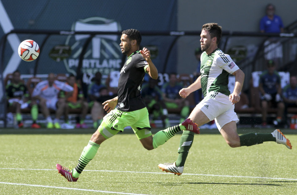 Photo - Seattle Sounders' Lamar Neagle, left, vies for control of the ball against Portland Timbers' Danny O'Rourke, right, during an MLS soccer game in Portland, Ore., Sunday, Aug. 24, 2014. (AP Photo/Natalie Behring)