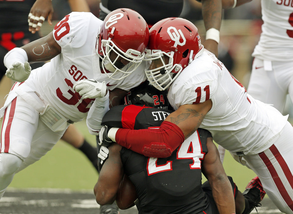 Photo - OU's R.J. Washington (11) collides with Javon Harris (30) as he brings down Texas Tech's Erich Stephens Jr. (24) during a college football game between the University of Oklahoma (OU) and Texas Tech University at Jones AT&T Stadium in Lubbock, Texas, Saturday, Oct. 6, 2012. Photo by Nate Billings, The Oklahoman