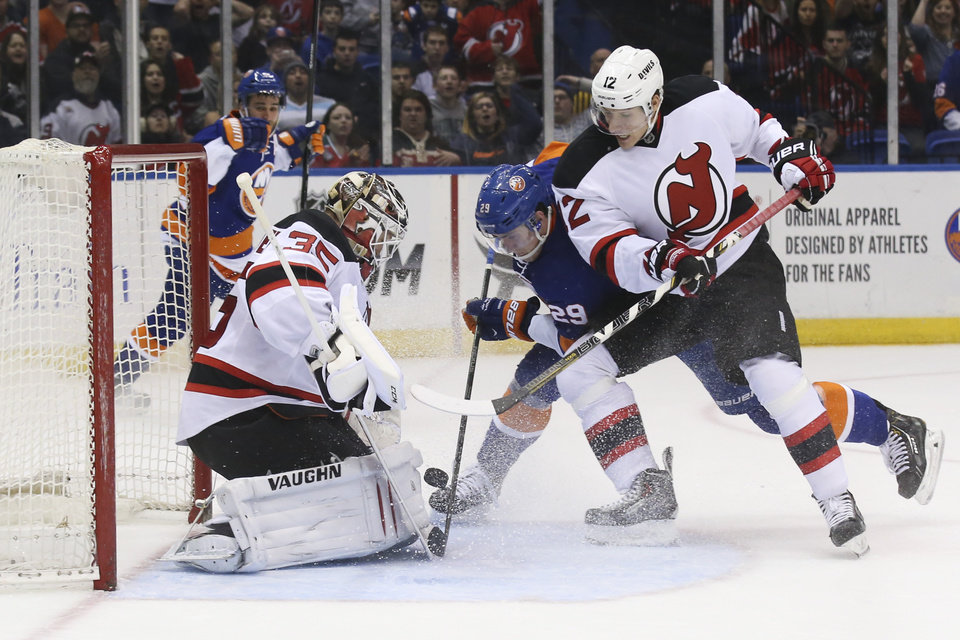 Photo - New Jersey Devils goalie Cory Schneider (35) makes a save against New York Islanders center Brock Nelson (29) as Devils right wing Damien Brunner (12) defends in the second period of an NHL hockey game on Saturday, March 29, 2014, in Uniondale, N.Y. (AP Photo/John Minchillo)