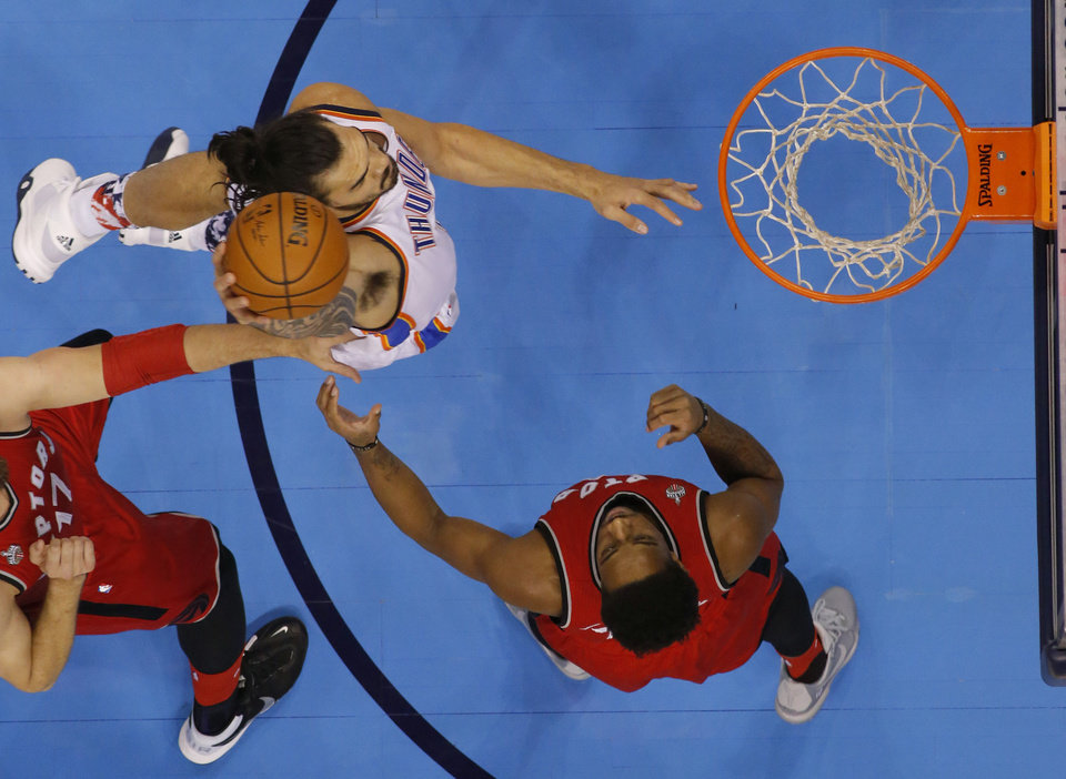 Photo - Oklahoma City's Steven Adams (12) dunks the ball beside Toronto's DeMar DeRozan (10) during an NBA basketball game between the Oklahoma City Thunder and the Toronto Raptors at Chesapeake Energy Arena on Wednesday, Nov. 4, 2015. Photo by Bryan Terry, The Oklahoman
