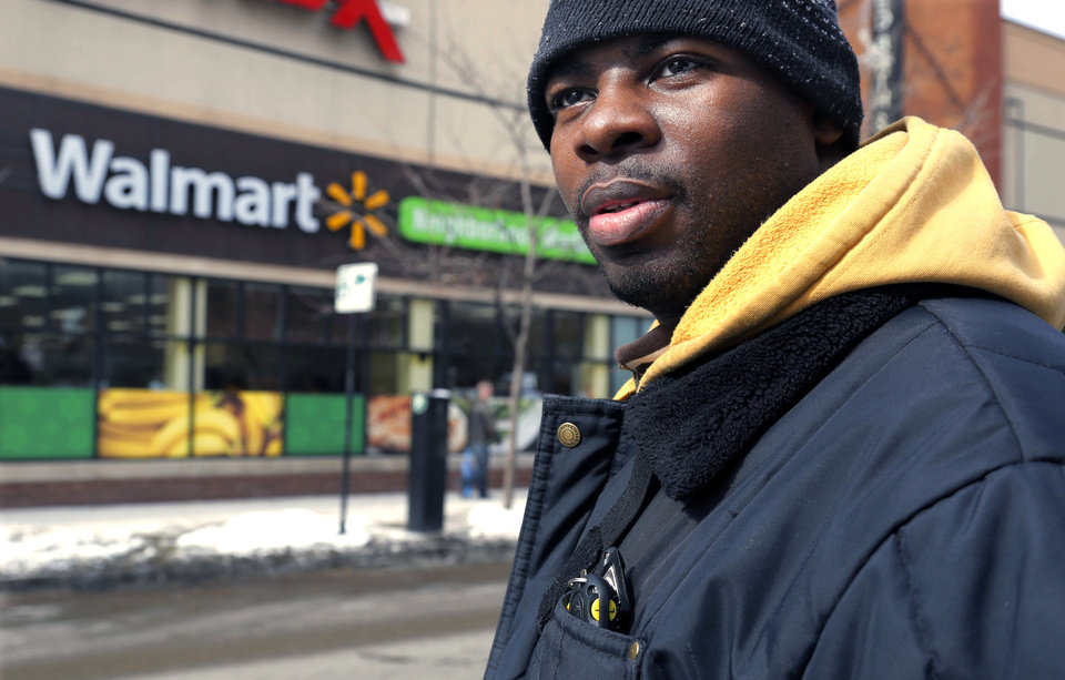 Photo - In this Tuesday, March 4, 2014, photo, Wal-Mart employee Richard Wilson, 27,  is photographed outside the store where he works in Chicago. Wilson earns $9.25 an hour at that Wal-Mart and lives on the city's western edge with his grandmother. (AP Photo/M. Spencer Green, File)