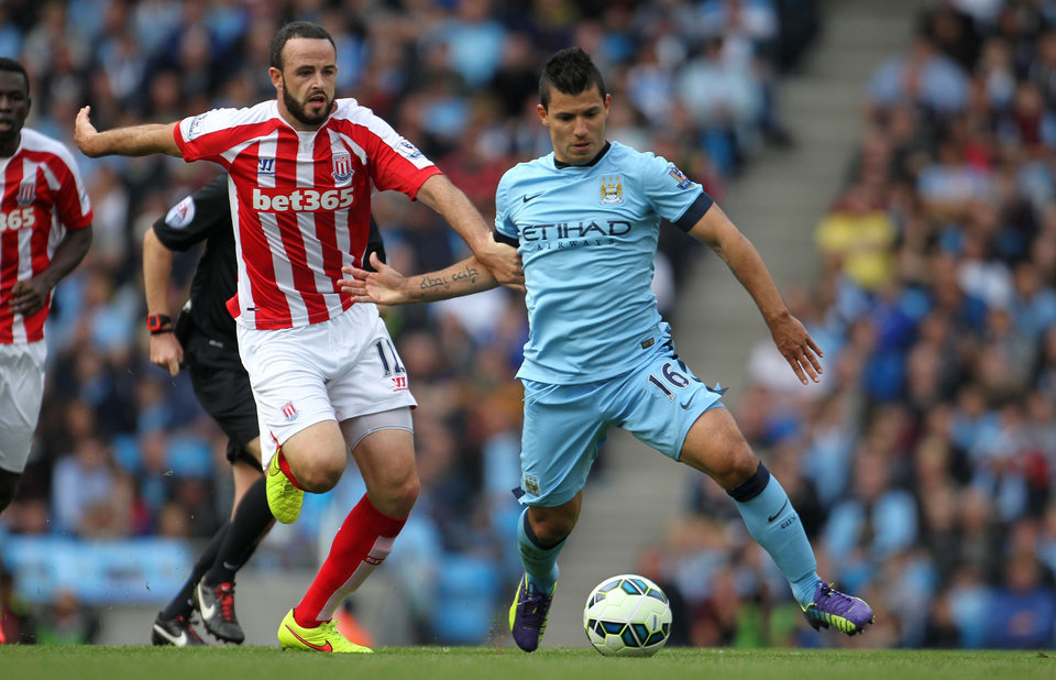 Photo - Stoke City's Marc Wilson, left, and Manchester City's Sergio Aguero battle for the ball during their English Premier League soccer match at the Etihad Stadium, Manchester, England, Saturday, Aug. 30, 2014. (AP Photo/Lynne Cameron, PA Wire)     UNITED KINGDOM OUT    -   NO SALES   -   NO ARCHIVES