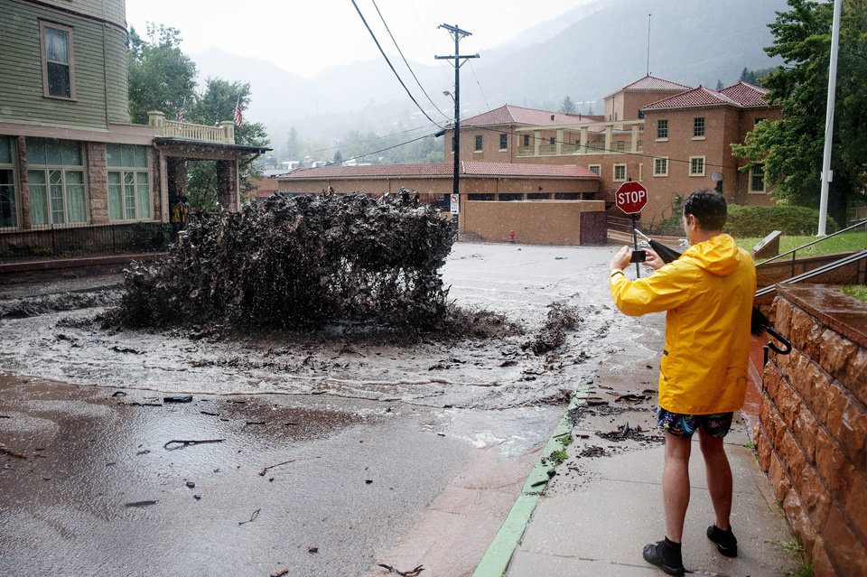 Photo - John Shada, of Manitou Springs, Colo., takes a photo of flood water as it shoots out of a sewer on Canon Avenue on Thursday, Sept. 12, 2013, in Manitou Springs, Colo. Flash flooding in Colorado has cut off access to towns, closed the University of Colorado in Boulder and left at least three people dead. (AP Photo/The Colorado Springs Gazette, Michael Ciaglo)