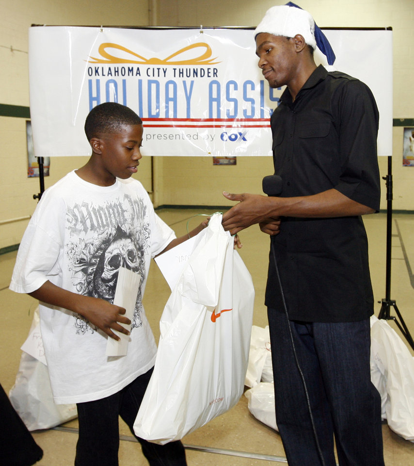 Photo - CHARITY / DONATE / DONATION / CHILD / KIDS: NBA basketball player Kevin Durant, right, of the Oklahoma City Thunder gives a bag of winter clothing to Lamar Brent, 14, during a holiday party for children in the after school program at Pilot Recreation Center, 1435 NW 2nd Street, in Oklahoma City, Wednesday, Dec. 17, 2008. At the end of the party, Kevin Durant gave the children winter coats, hats and gloves donated by Nike. BY NATE BILLINGS ORG XMIT: KOD