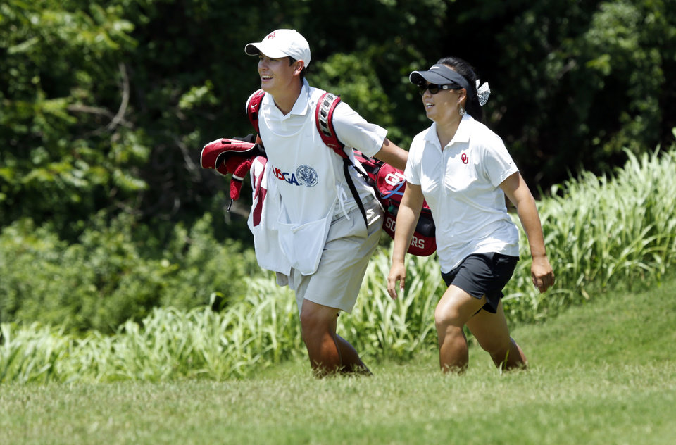 Photo - U.S. WOMEN'S AMATEUR PUBLIC LINKS CHAMPIONSHIP GOLF TOURNAMENT: Chirapat Jao-Javanil, Norman, Okla. and her caddy Chad Smith walk toward 2 green as she plays against Raychelle Santos, La Quinta, Calif. in the round of 16 during the USGA Women's Public Links championship at Jimmie Austin OU Golf Course on Thursday, June 20, 2013, in Norman, Okla.  Photo by Steve Sisney, The Oklahoman