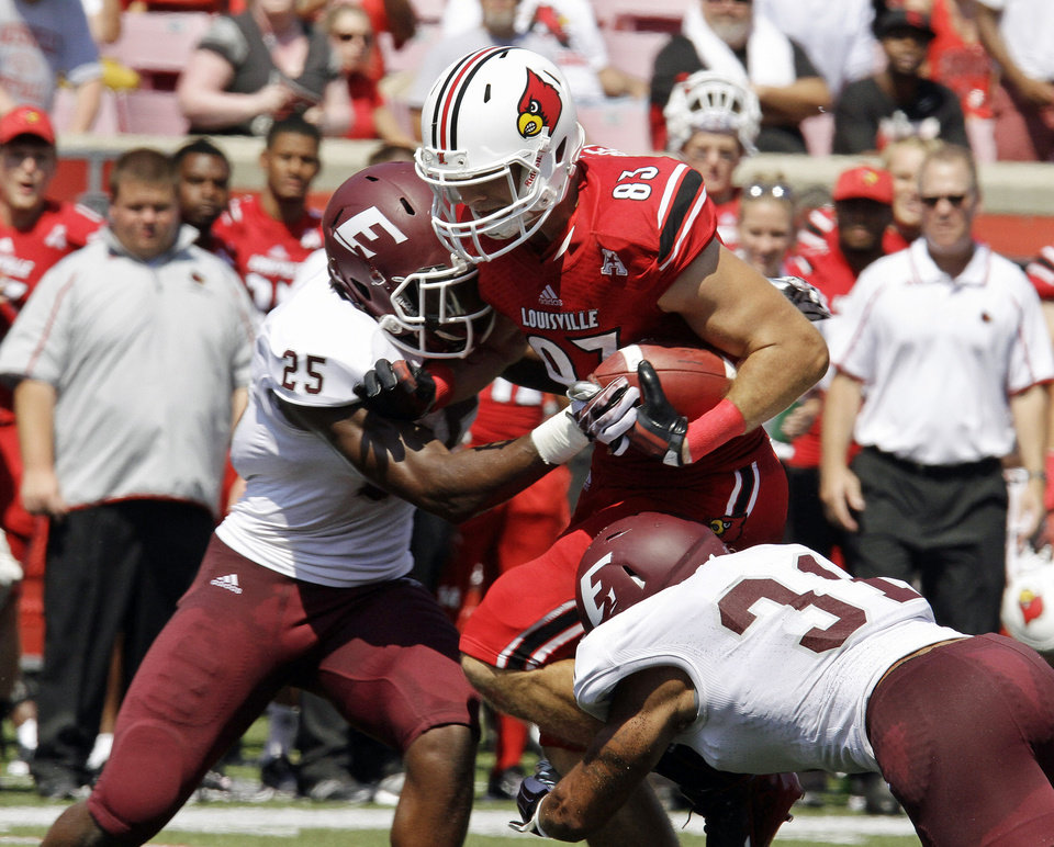 Photo - Louisville tight end Ryan Hubbell (83) gets hit from both sides by Eastern Kentucky tacklers Chris Owens (25) and Christian Albertson (31) after this pass catch in the first quarter of their NCAA college football game in Louisville, Ky., Saturday, Sept. 7, 2013. (AP Photo/Garry Jones)