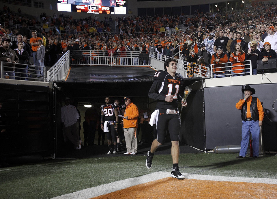 Photo - OSU's Zac Robinson (11) runs on the field before the college football game between Oklahoma State University (OSU) and the University of Colorado (CU) at Boone Pickens Stadium in Stillwater, Okla., Thursday, Nov. 19, 2009. Photo by Sarah Phipps, The Oklahoman