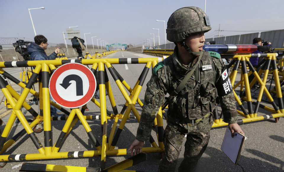 Photo - A South Korean army soldier moves a part of barricade for the media to enter at Unification Bridge near the border village of Panmunjom, that has separated the two Koreas since the Korean War, in Paju, north of Seoul, South Korea, Tuesday, April 9, 2013. North Korean workers didn't show up for work at a jointly run factory complex with South Korea on Tuesday, a day after Pyongyang suspended operations at the last remaining major economic link between rivals locked in an increasingly hostile relationship. (AP Photo/Lee Jin-man)