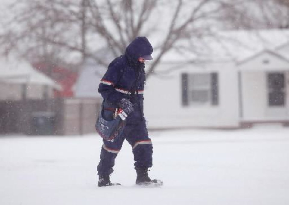 Photo - Mail carrier David Alexander lowers his head and walks through snow delivering mail in a Midwest city neighborhood near SE 15 and Lockheed. Alexander, who has worked for the post office for 26 years, said the most difficult part of delivering the mail in this weather is walking through the snow. He said the sub-freezing temperatures don't bother him too much because he dresses for the cold. He wears five layers of clothing above the waist and three layers of clothing below the waist. He wears thermal undershirts and pants. On his feet, he wears boots. He wears gloves and a mask around his face. A second winter storm in a week dumped about 6 inches of snow in the Oklahoma City area Tuesday morning, Feb. 9, 2011. Photo by Jim Beckel
