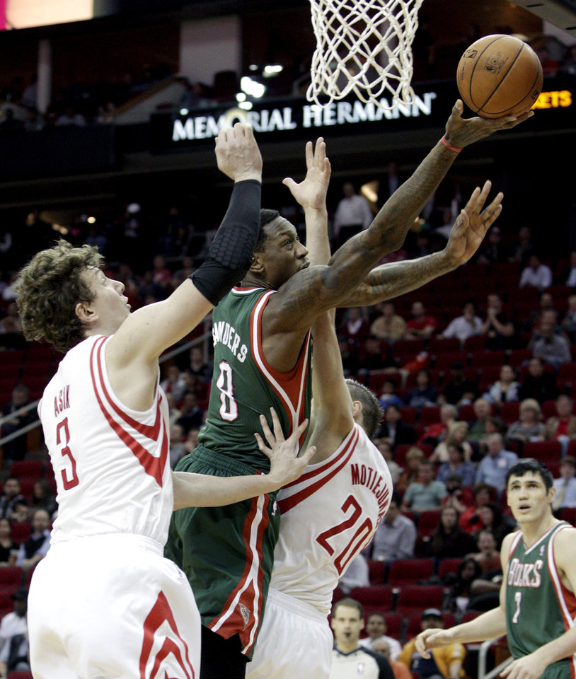 Milwaukee Bucks center Larry Sanders (8) drives to basket between Houston Rockets center Omer Asik (3) and forward Donatas Motiejunas (20) during the first half of an NBA basketball game, Wednesday, Feb. 27, 2013 in Houston. (AP Photo/Bob Levey)