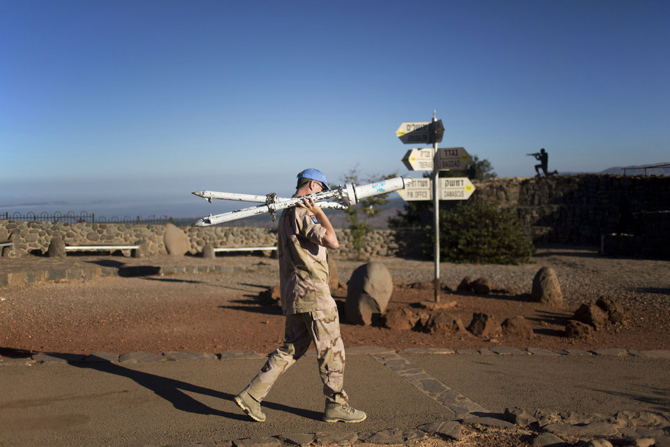 Photo - A U.N. peacekeeper from the United Nations Disengagement Observer Force, also known as UNDOF, walks at an observation point on Mt. Bental in the Israeli-controlled Golan Heights, overlooking the border with Syria, Thursday, Aug. 28, 2014. From the Israeli side of the de facto border, large clouds of smoke could be seen, as gunfire and explosions sounded in the distance. Israeli soldiers observed the fighting. (AP Photo/Ariel Schalit)