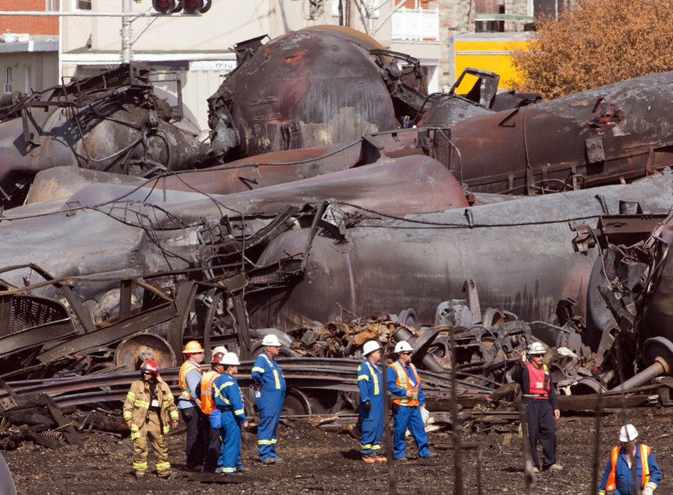 Photo - File- In this July 6, 2013 file photo, workers stand before mangled tanker cars at the crash site of the train derailment and fire in Lac-Megantic, Quebec, Canada. On the tranquil bank of the Columbia River in Vancouver, Wash., just across from Portland, Ore., regulators are weighing the fate of what could become the Pacific Northwest's largest crude oil train terminal: it would receive daily shipments of up to 360,000 barrels of oil via four trains a day rolling through iconic river communities and into the crowded Portland/Vancouver metro area, each train 120 cars and more than a mile long.  (AP Photo/Ryan Remiorz, Pool, File)