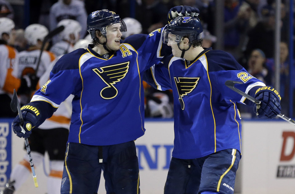 Photo - St. Louis Blues' Kevin Shattenkirk, right, is congratulated by T.J. Oshie after scoring the game-winning goal during a shootout of an NHL hockey game against the Philadelphia Flyers Tuesday, April 1, 2014, in St. Louis. The Blues won 1-0. (AP Photo/Jeff Roberson)