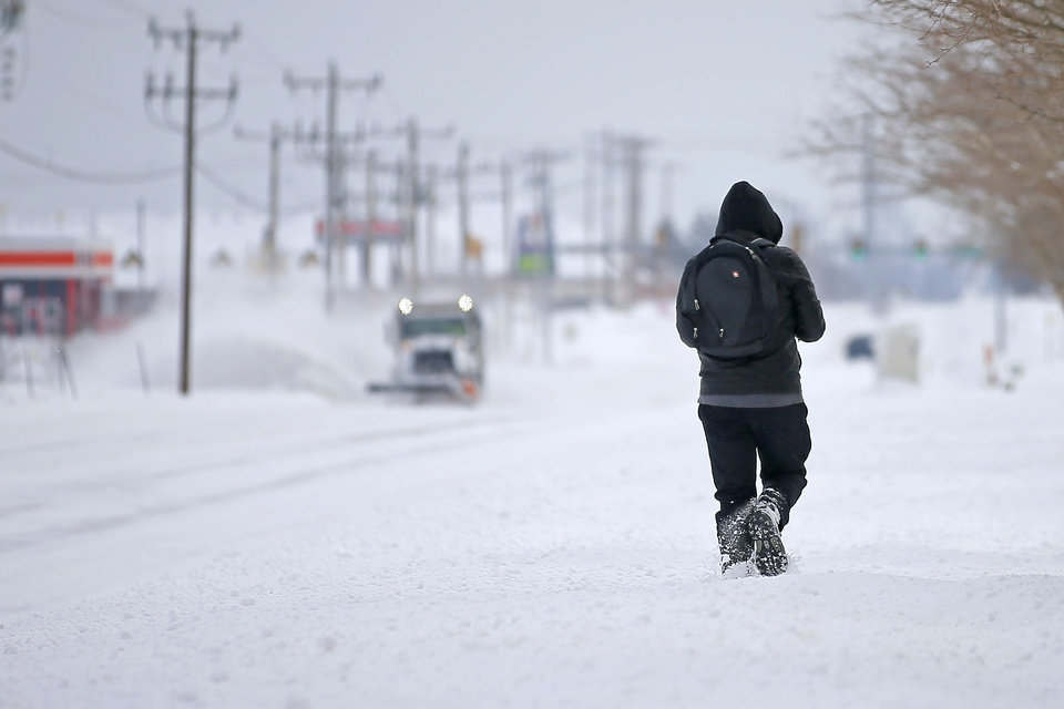 Photo - A man walks along NW 164 as an Oklahoma City Public Works truck plowing snow approaches in northwest Oklahoma City after a winter storm dropped another layer of snow in Oklahoma City, Wednesday, Feb. 17, 2021. [Bryan Terry/The Oklahoman]