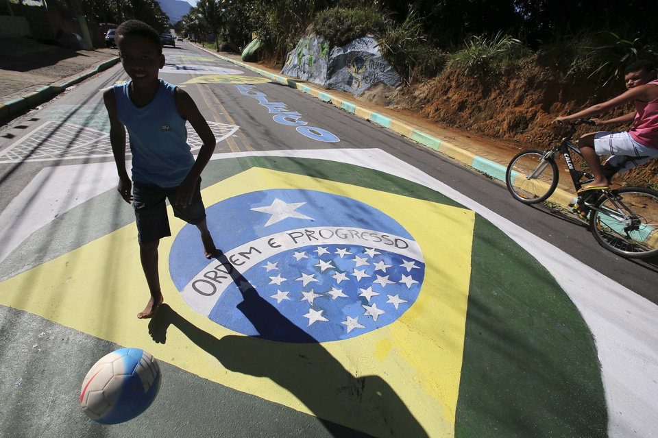 Photo - A youth plays soccer on a street decorated with World Cup related murals in Mangaratiba, Brazil, Thursday, June 12, 2014. The World Cup soccer tournament starts today. (AP Photo/Antonio Calanni)