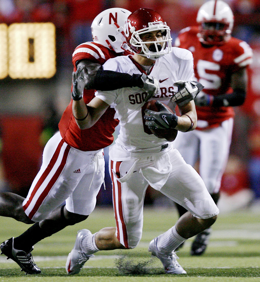 Oklahoma's Cameron Kenney (6) is brought down by Nebraska's Larry Asante (4) during the first half of the college football game between the University of Oklahoma Sooners (OU) and the University of Nebraska Cornhuskers (NU) on Saturday, Nov. 7, 2009, in Lincoln, Neb.