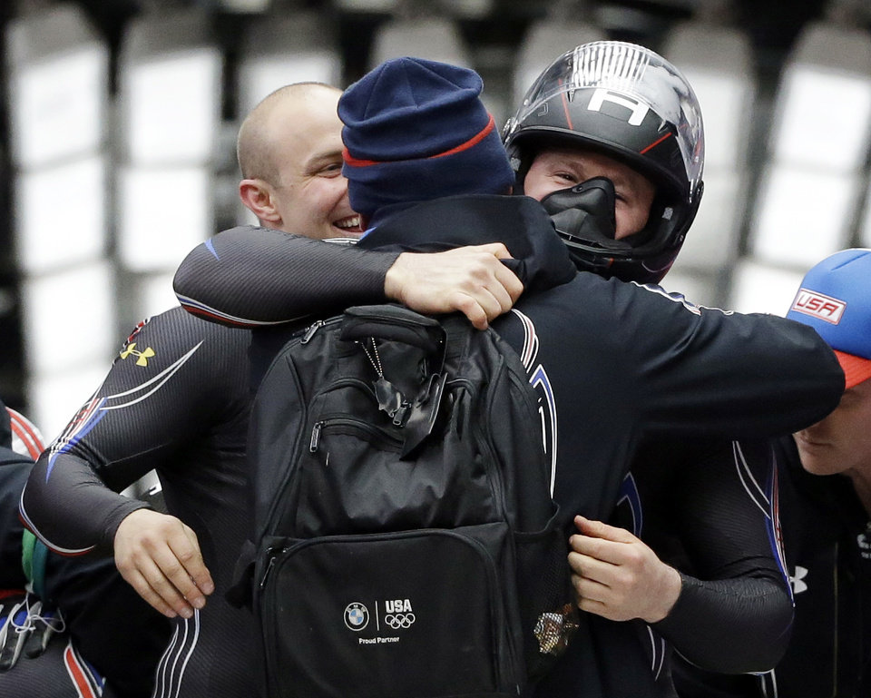 Photo - The team from the United States USA-1, pilot Steven Holcomb gets hugged by teammates after his bronze medal finish during the men's two-man bobsled competition at the 2014 Winter Olympics, Monday, Feb. 17, 2014, in Krasnaya Polyana, Russia. (AP Photo/Dita Alangkara)