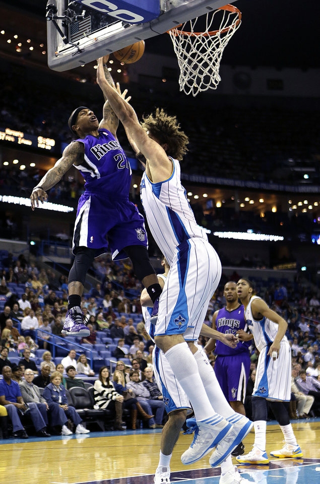 Photo - Sacramento Kings point guard Isaiah Thomas (22) goes to the basket against New Orleans Hornets center Robin Lopez during the first half of an NBA basketball game in New Orleans, Sunday, Feb. 24, 2013. Thomas was called for an offensive foul on the play.  (AP Photo/Gerald Herbert)