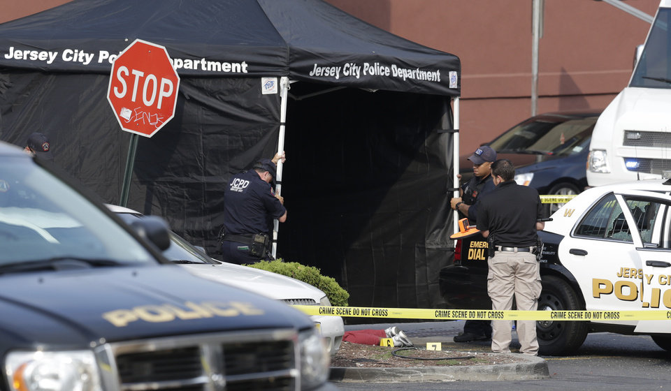 Photo - A person lays on the ground near evidence markers as officials use a tent while investigating the scene where a Jersey City Police Department officer was shot and killed while responding to a call at a 24-hour pharmacy, Sunday, July 13, 2014, in Jersey City, N.J. Officer Melvin Santiago was shot in the head while still in his police vehicle as he and his partner responded to an armed robbery call  at about 4.a.m., Jersey City Mayor Steven Fulop said in a statement.  Fulop said officers responding to the robbery call shot and killed the man who shot Santiago. He was not immediately identified.(AP Photo/Julio Cortez)
