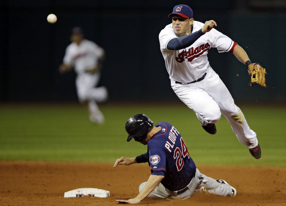 Photo -   Cleveland Indians shortstop Asdrubal Cabrera throws over Minnesota Twins' Trevor Plouffe but fails to complete a double play on Twins' Chris Herrmann as a run scores in the fifth inning of a baseball game, Wednesday, Sept. 19, 2012, in Cleveland. (AP Photo/Mark Duncan)