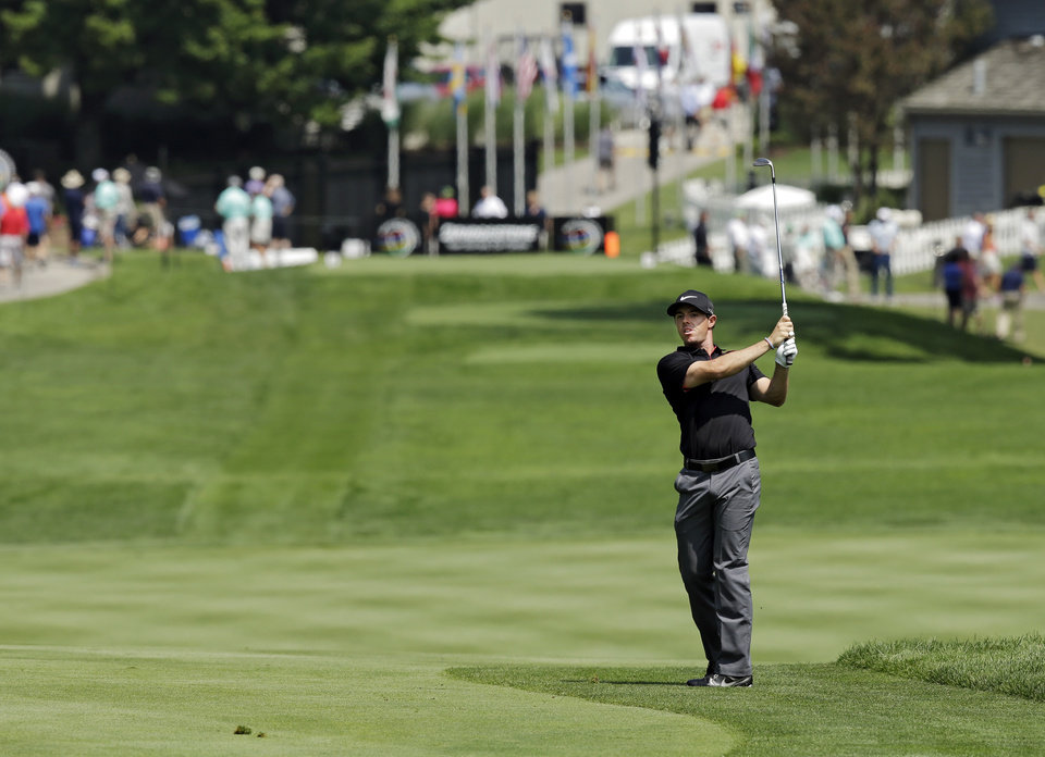 Photo - Rory McIlroy, from Northern Ireland, watches his approach shot to the 17th green during the first round of the Bridgestone Invitational golf tournament Thursday, July 31, 2014, at Firestone Country Club in Akron, Ohio. (AP Photo/Mark Duncan)