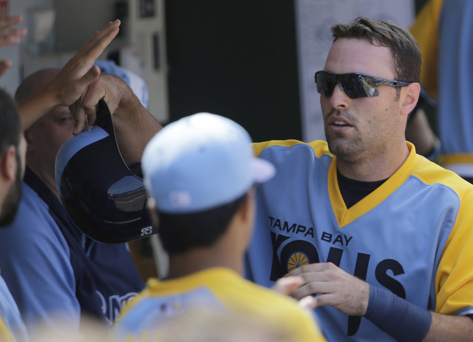 Photo - Tampa Bay Rays' Curt Casali, right, celebrates with teammates after scored scores on a single hit by Desmond Jennings during the fifth inning of an interleague baseball game against the Chicago Cubs in Chicago, Sunday, Aug. 10, 2014. (AP Photo/Nam Y. Huh)