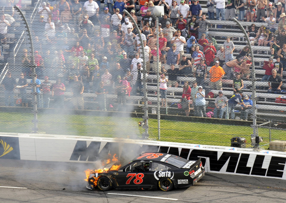 Photo - Kurt Busch's car burns after he hit the wall in the first turn during the STP 500 NASCAR Sprint Cup series auto race at Martinsville Speedway in Martinsville, Va., Sunday, April 7, 2013.  (AP Photo/Don Petersen)