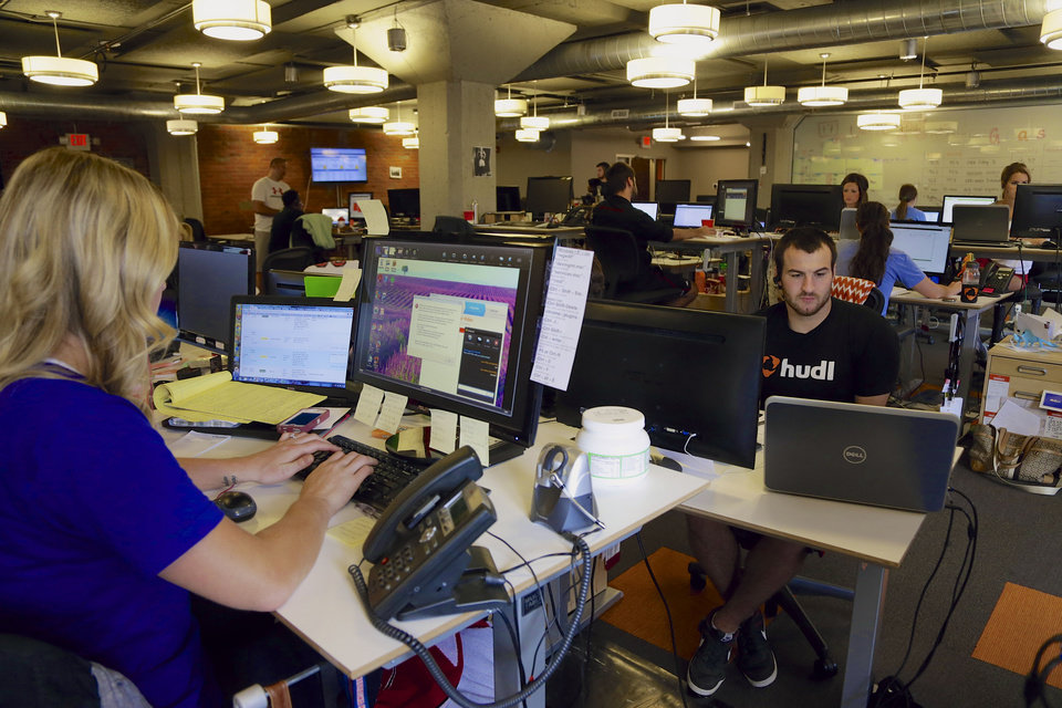 Photo - In this photo from Aug. 14, 2014, support team members work at their stations at Hudl, in Lincoln, Neb. Hudl is a software company that has developed a way to immediately get game film to coaches after games and break down and separate different plays by type. (AP Photo/Nati Harnik)