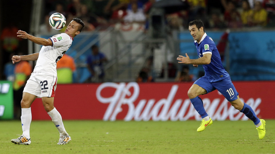 Photo - Costa Rica's Jose Miguel Cubero, left, controls the ball chased by Greece's Giorgos Karagounis during the World Cup round of 16 soccer match between Costa Rica and Greece at the Arena Pernambuco in Recife, Brazil, Sunday, June 29, 2014. (AP Photo/Ricardo Mazalan)