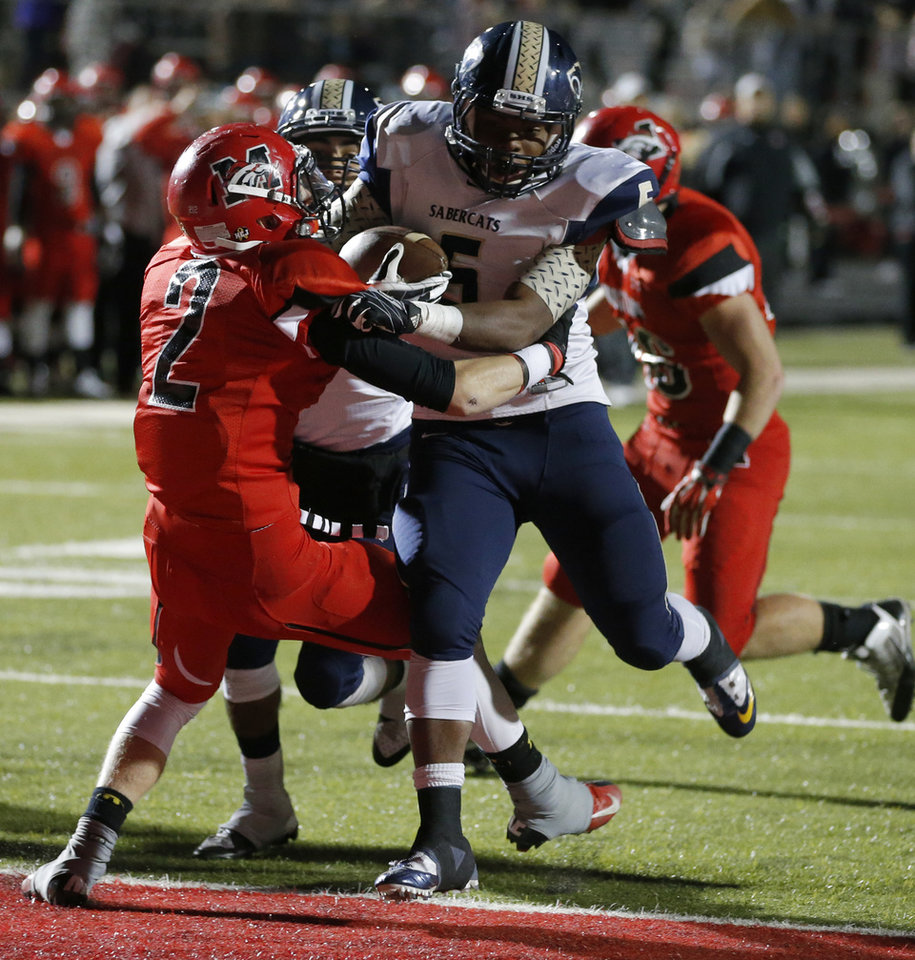 Photo - Southmoore's Pierce Spead scores a touchdown beside Mustang's Tanner Robertson during their high school football game in Mustang, Okla., Friday, November 8, 2013. Photo by Bryan Terry, The Oklahoman