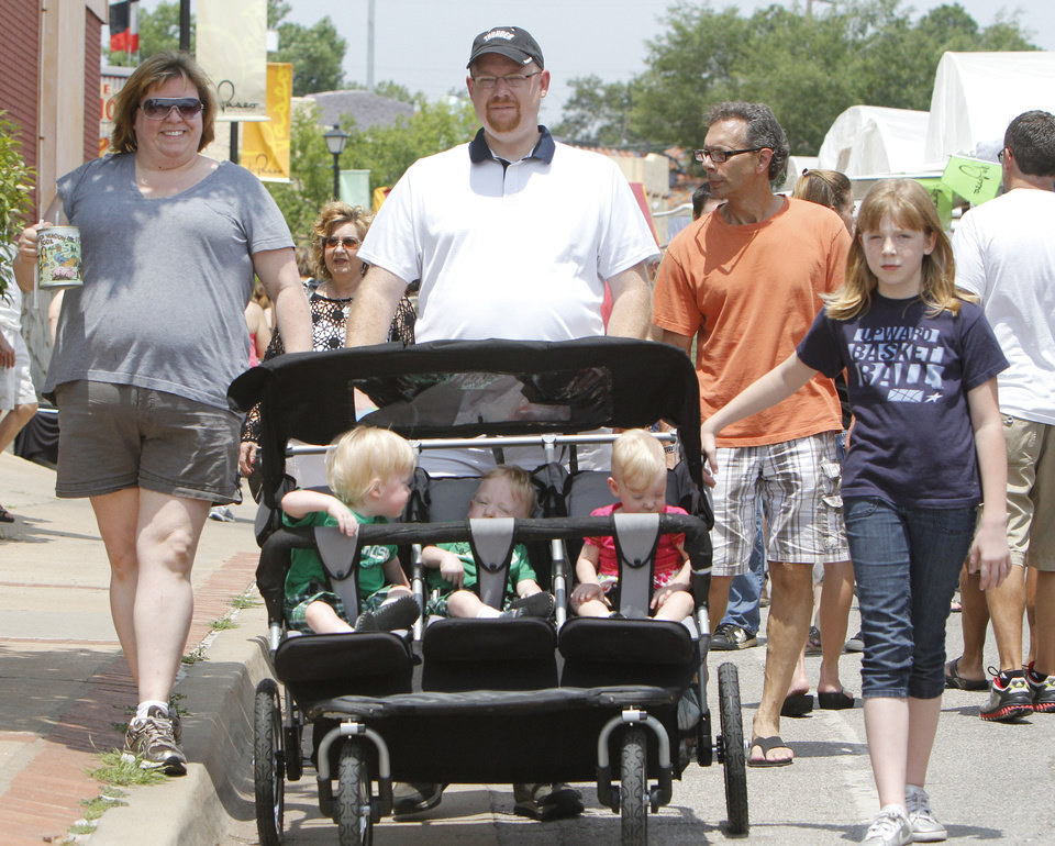 Photo - Dara McMillin (left), Michael, and 10 year old Kiera, push 18 month old triplets Eli, Easton, and Elliana, during the Paseo Arts Festival in Oklahoma City, OK, Saturday, May 26, 2012,  By Paul Hellstern, The Oklahoman