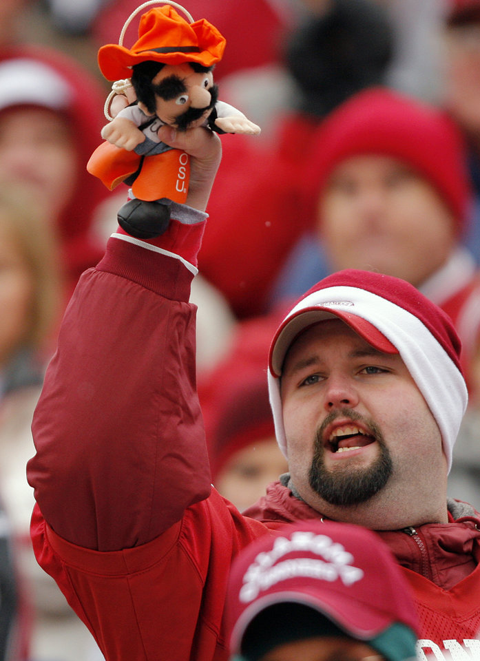 Photo - An Oklahoma fan cheers on his Sooners during the first half of the college football game between the University of Oklahoma Sooners (OU) and the Oklahoma State University Cowboys (OSU) at the Gaylord Family-Memorial Stadium on Saturday, Nov. 24, 2007, in Norman, Okla. 