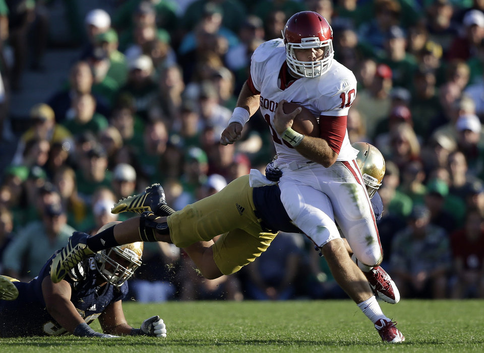Oklahoma's Blake Bell (10) runs out of the tackle of Notre Dame 's Dan Fox during the second half of an NCAA college football game on Saturday, Sept. 28, 2013, in South Bend, Ind. Oklahoma defeated Notre Dame 35-21. (AP Photo/Darron Cummings) ORG XMIT: INDC118