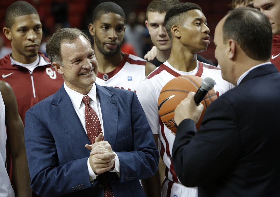 Photo - Joe Castiglione, athletic director at the University of Oklahoma, presents coach Lon Kruger with the game ball for his 500th win during a men's college basketball game between the University of Oklahoma and Northwestern Louisiana State University at the Lloyd Noble Center in Norman, Okla., Friday, Nov. 30, 2012.  Photo by Garett Fisbeck, The Oklahoman