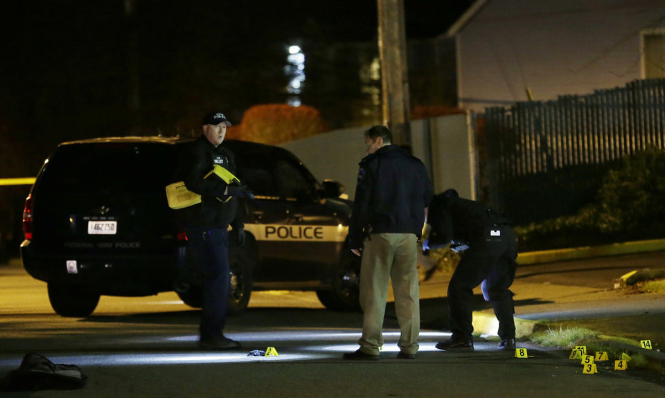 Photo - Police officers stand near evidence markers at the scene of an overnight shooting that left five people dead, Monday, April 22, 2013, at the Pinewood Village apartment complex in Federal Way, Wash. (AP Photo/Ted S. Warren)