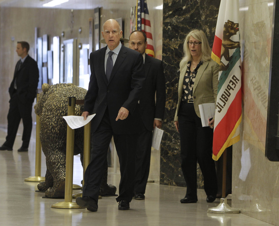 Gov. Jerry Brown leaves his office to attend a news conference where he discussed the passage of his tax initiative, Proposition 30, in Sacramento, Calif., Wednesday, Nov. 7, 2012. Brown called the voter approved measure, that will place a temporary increase on the state sales tax and on the wealthy with the proceeds earmarked for education, a