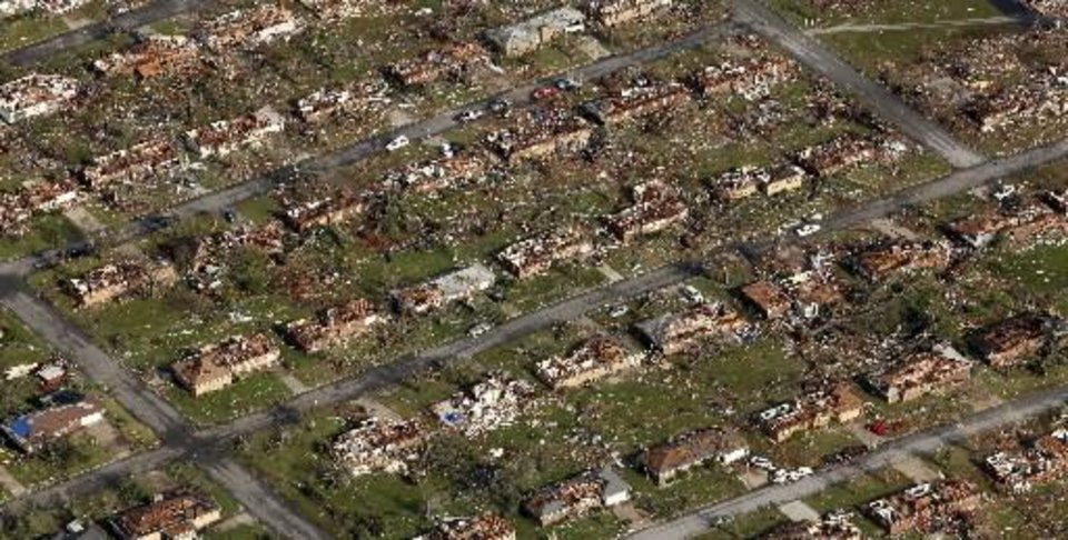 Photo - This aerial photograph shows a neighborhood destroyed by a powerful tornado in Joplin, Mo. Tuesday, May 24, 2011. A tornado moved through much of the city Sunday, damaging a hospital and hundreds of homes and businesses and killing at least 116 people. (AP Photo/Charlie Riedel)
