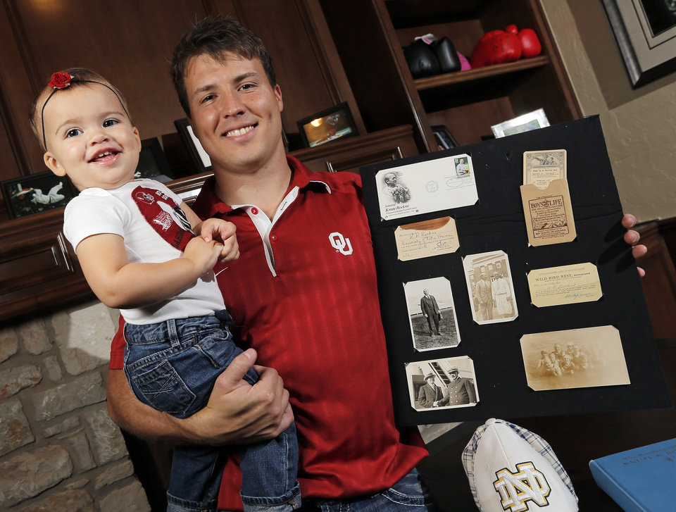 Photo - Former OU cheerleader Chris Knute Kochendorfer holds his daughter Jemma Kochendorfer, one-and-a-half, as he poses for a picture with memorabilia of his great grandfather, legendary Notre Dame football coach Knute Rockne, at Kochendorfer's home in Oklahoma City, Wednesday, Oct. 24, 2012. Photo by Nate Billings, The Oklahoman