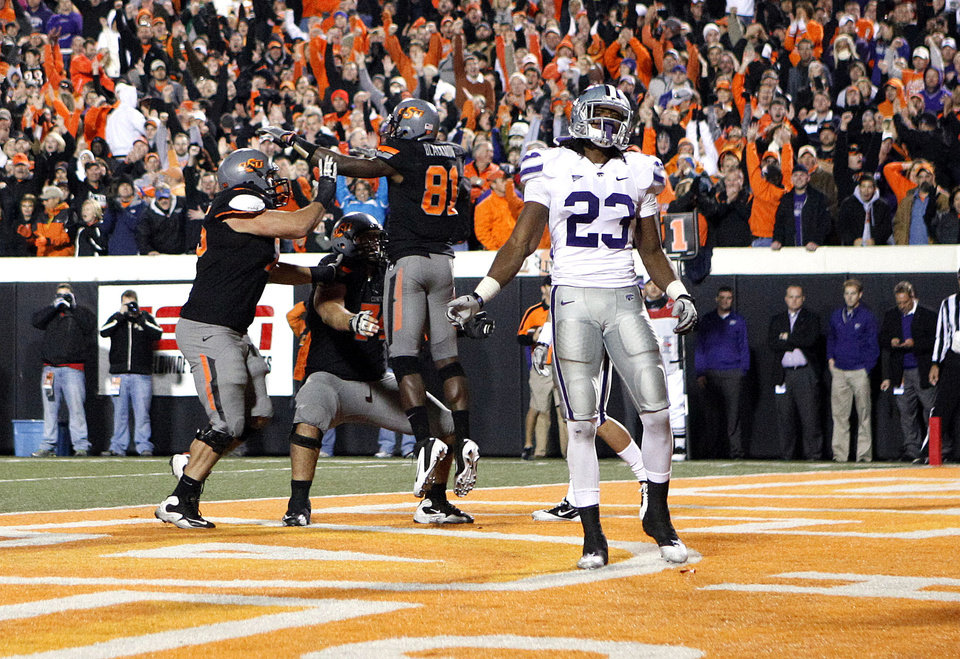 Photo - Kansas State's Emmanuel Lamur (23) reacts as Oklahoma State's Nick Martinez (75), Grant Garner (74) and Justin Blackmon (81) celebrate a touchdown late in the fourth quarter during a college football game between the Oklahoma State University Cowboys (OSU) and the Kansas State University Wildcats (KSU) at Boone Pickens Stadium in Stillwater, Okla., Saturday, Nov. 5, 2011.  Photo by Sarah Phipps, The Oklahoman