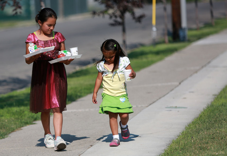 Photo -       Angeles Alfaro carries dinner for her and her sister Jasmine Alfaro outside of the Central Park Community Center in South Salt Lake on Friday, July 18, 2014. The dinner is part of the Salt Lake CAP summer food program, which offers free dinner to children at five locations in the valley, Monday through Friday.