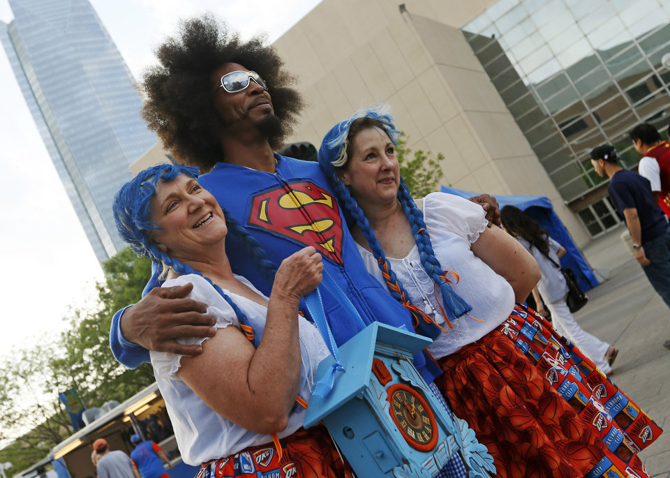 Photo - Cheri Rich, left, and Vanessa Shadix, right, dress in Thunder-themed Swiss costumes as they pose for a photo with Cedric Owens, aka Afro Thunder, before Game 5 in the first round of the NBA playoffs between the Oklahoma City Thunder and the Houston Rockets at Chesapeake Energy Arena in Oklahoma City, Wednesday, May 1, 2013. The women wore the costumes to root for Swiss Thunder player Thabo Sefolosha.  Photo by Nate Billings, The Oklahoman
